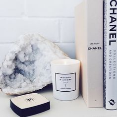Bedside table inspiration featuring a simple white candle, Chanel decor, and a luxurious crystalized geode rock.
