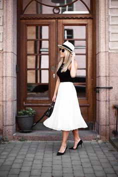 White midi skirt. Black top. Hat.