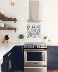 Minimalist modern farmhouse kitchen with white shiplap backsplash, reclaimed wood shelves and Sherwin Williams Inkwell cabinets with satin gold cabinet pulls.