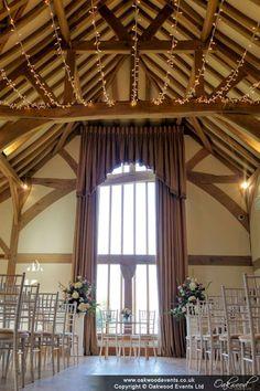 An autumn wedding, looking down the aisle under a fairy light canopy at Cain Manor.