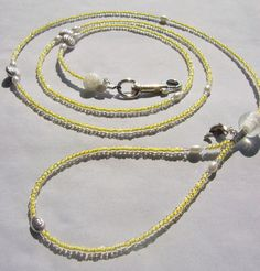 Sunshine Dog Leash Its Bright  Its cheery  and its Yellow!    Made with Sunshine Yellow inside colored Glass Beads  Fresh Water Pearls  Swarovski Crystals  Sterling Silver  and Silver Puff Spacers    A medium size Clear Glass Ball sits at the base of the handle with a Dolphin Charm right above it.  A smaller off White Rose Ball sits at the end of the leash with a Silver Sea Shell Charm below it.    Free Shipping in USA    INTERNATIONAL BUYERS  Please contact owner for International Rates and…