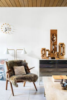 The living room in Mark Neely and Paul Kefalides's Eichler is decked out with the couple's vintage finds, including a Hans Wegner Sawback chair (the fur throw obscures an area needing repair), a George Nelson Ball Clock, a DF-2000 cabinet by Raymond Loewy, a light designed by Greta Von Nessen, and a suite of Brian Willshire wooden sculptures, one of Neely's many collections.  Photo by Drew Kelly.