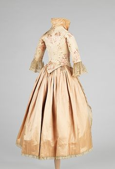 This is an elaborate evening dress, c 1885, made for a child. It is unusual to see a fully boned and fitted bodice made in this small of a size, possibly for a six to eight year old. It is very possible that the fabric of this dress may have come from a women's dress for a special party.