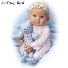 Poseable and weighted baby doll in pink-and-white ensemble, floral headband. Hand-painted RealTouch® vinyl skin, hand-rooted hair. Matching teddy.