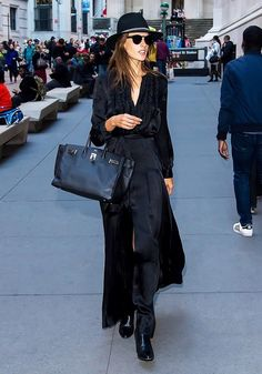 Alessandra Ambrosio wears a black maxi dress with a black felt hat and an Hermès handbag before the VS fashion show.