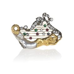 "A Victorian silver-topped 18 karat gold, diamond, emerald, ruby and pearl brooch, featuring a depiction of the penultimate scene from the fable ""Jack and the Beanstalk"" in which Jack lures the giant by stealing the mermaid harp. A baroque pearl forms the tail of a sculpted 18-karat gold mermaid decorating the base of a lyre outlined with old mine-cut diamonds. The strings of the lyre are accented with emeralds, rubies, diamonds and a sapphire."