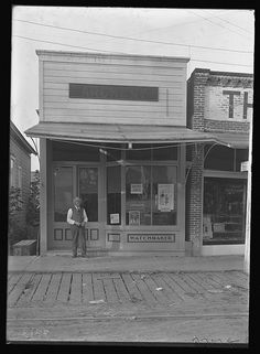 """Captain F.S. Barnes standing outside his Archery shop. Posters in window for the Pasmore Trio concert, also sign on outside of building says """"Watchmaker"""". 1910.  Forest Grove, Oregon"""
