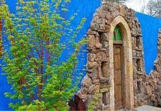 Stone garden entry with blue stucco walls