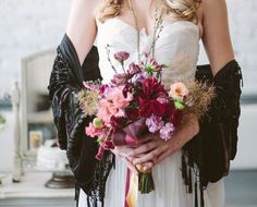 bride with dark velvet scarf and bouquet filled with dark pink flowers