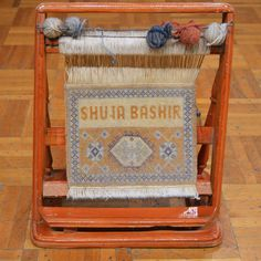 Miniature rug weaving loom given to Mr Bashir as a gift by a client.This hand loom showcases an horizontal frame placed on the ground with colored yarn tied to the wool web to create the carpet.Traditional skills of carpet weaving are an art form that date back to centuries. They are shared among families of weavers where mothers traditionally train their daughters to use the materials, tools and skills, while fathers train their sons in shearing wool and making looms.