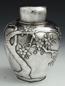 Japanese Sterling Antique Tea Caddy  A fine quality Japanese sterling silver tea caddy with pull off cap and interior push in cap. The surface has very fine hammering with an embossed tree with blossoms circumventing the entire caddy. Marked with the retailer, sterling and Japanese letters.   Circa 1900