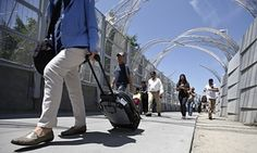 Pedestrians pull suit cases and newly bought goods as they trek up the new pedestrian walkway to the Mexico border crossing in San Ysidro, California. Starting late Wednesday, Aug. 19, pedestrians going to Tijuana from San Diego at the San Ysidro crossing must choose between a line for Mexicans who get waved through, and a line for foreigners. Foreigners must show a passport, fill out a form and - if staying more than a week - pay for a six-month permit. (AP Photo/Lenny Ignelzi)