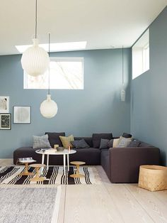 Plenty of seating in this modern minimalist living room. The large pendant lights help fill out the space created by the high ceilings.