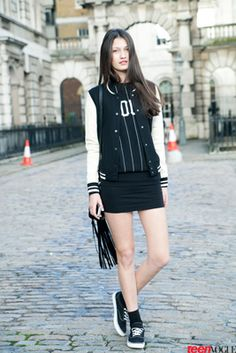 Model Kelly gets sporty in a black and white H&M varsity jacket and baseball T-shirt.