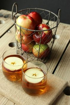 hot apple and pear spiced cider served in stemless wine glasses with a thing slice of apple floating on top.