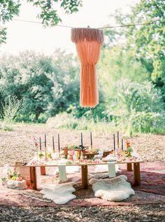 Eine kreative Tafel im Freien. Die Gäste werden auf gemütliche Schafsfelle, statt Stühle gebettet. Farbenfrohe Elemente und als i-Tüpferl hängt über dem Tisch eine Gardine.