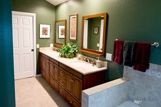 A wooden vanity contrasts beautifully against the dark green walls and white accents in this One Week Bath transitional bathroom remodel. Our transitional bath renovation uses both traditional style and contemporary style, a great idea for those who can't choose a favorite bathroom design. Need help? Contact us for your bathrooom remodeling needs! #OneWeekBath #Green #Bathroom