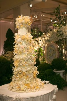 The couple's tall wedding cake was embellished with sugar flowers in hues of ivory and gold. Each tier featured it's own flavor of cake, including white, chocolate, pistachio, and chocolate chip. #FloralWeddingCake Photograph by: Jose Villa Photography. Read More: https://www.insideweddings.com/weddings/destination-beverly-hills-wedding-with-celebrity-chef-performers/467/