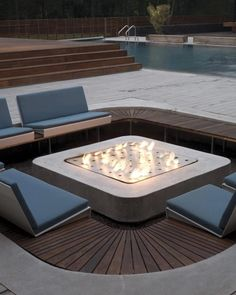 Sunken fire pit/seating area in patio. Chocolate brown wood color, blue gray cushions and gray patio surface help define a look that is both streamlined and cozy.