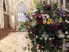 Pedestal arrangement of seasonal country wedding flowers at Charlecote Park church. Flowers by Honey Pot Flowers