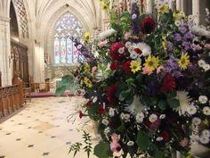 Pedestal arrangement of seasonal country wedding flowers at Charlecote Park church. Flowers by Honey Pot Flowers