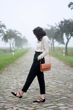 Black pants, white blouse, with leather purse and pointed shoes as accents