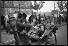 Jiangsu. Nankin. April 1949. With their few belongings piled in a fiacre, a soldier and a boy flee the city just ahead of the Communist Army. In the background, the makeshift dwellings shelter the thousands of refugees of this civil war. - Henri Cartier-Bresson