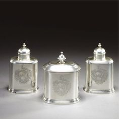 A pair of George II silver tea caddies and a matching sugar box and cover, mark of John Newton, London, 1740 oval, the caddies with detachable domed covers, sliding bases, lead liners, armorial engraved, marked on the necks only with cancelled London Assay Office marks, the sugar box armorial engraved, fully hallmarked on underside