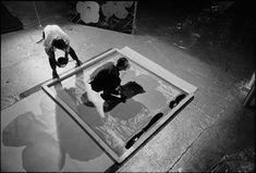 Andy Warhol and Gerard Malanga silkscreening a flower painting by David McCabe (1965)