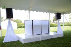 White DJ booth with white speaker stand covers and white stage under outdoor tent.