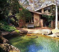 Casa de campo com lago frontal. Acabamento em pedra natural, blocos= cerâmico.