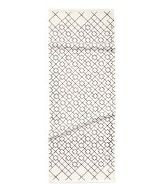 White. Rectangular, woven cotton rug with a printed pattern at front.