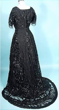 "1912 Black Sequin, Beading and Lace Trained Evening Gown! $2450. ""lack lace gown teeming with black sequins in a design of swirling fern frond bands diagonally placed to create a feeling of motion even when still! Jet beaded font and back bodice inserts, jet beaded fringe on the short sleeves, neckline and wraps diagonally across the torso. Boned bodice.  Black taffeta lining with ruffled hemline shorter than the gown so one can see the beaded/sequin pattern around the hemline."""
