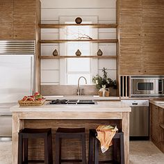 Wood softens the lines in this modern kitchen, and warm tones balance the industrial appearance of limestone countertops and stainless appliances.  NextGood Vibrations
