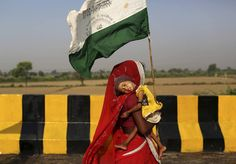 """A landless Indian farmer woman carries her child and marches during the """"Jan Satyagraha,"""" near Agra, India on Tuesday, Oct. 9, 2012. AP / Kevin Frayer"""