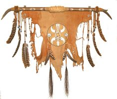 Deer Hide Buffalo Hunt Wall-hanging. This wall-hanging sculpture represents the buffalo hunt by the Plains Indians of the late 1800s. The symbol in the center represents the earth, the arrow the hunt, and the horns the buffalo as spirit surrounding the earth. The hawk feathers represent