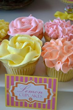 Rose- and hydrangea-topped cupcakes in hues of soft coral, baby pink and light yellow add to the floral theme.