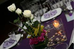 Rosas minimalistasModerno centro de mesa cuadrado en base de acrílico que en una parte lleva un pequeño ramillete de flores de diferentes tonos en cada capa, y acompañado de piedras de rio y velas que le darán un toque romántico.