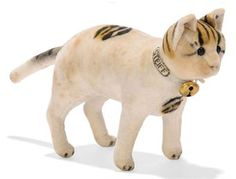 A STEIFF STANDING VELVET CAT, (1417,0), white with black and brown striped spots, black boot button eyes, pink stitching, 'STEIFF' ribbon with bell and small FF button, <I>circa 1907 --5¼in. (13.5cm.) long (some slight foxing)</I>