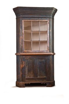 "Pennsylvania, late 18th-early 19th century, pine. One-piece cupboard with exaggerated, stepped cornice, nine-pane upper door, double-paneled lower door, and bracket feet. Cleaned down to old blue paint. Imperfections. 81 1/2""h. 48""w. 24""d."
