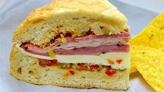 A homemade olive salad is spread on fresh bread which is then layered with salami, ham, mortadella, mozzarella and Provolone. Great sandwich, anyone?! Note: Use round bread loaves for real muffuletta.