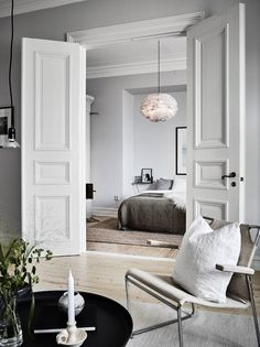 Classic elegance and Nordic minimalism paired in this living room and bedroom - - Classic elegance and Nordic minimalism paired in this living room and bedroom. Classic elegance and Nordic minimalism paired in this living room and bedroom. Home Bedroom Interior Barn Doors, Home Interior, Double Doors Interior, Apartment Interior, French Apartment, Apartment Door, Parisian Apartment, Dream Apartment, Bedroom Apartment