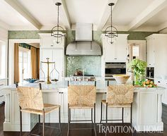 The kitchen's ivory cabinets, Calacatta Gold marble countertops, and shimmering, watery-tone backsplash tiles honor both sand and sea. - Photo: Erica Dines / Design: Tammy Connor