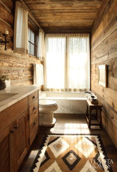 Luxurious marble sourced in Montana acts as a stylish counterpoint to the massive log construction in this master bathroom.
