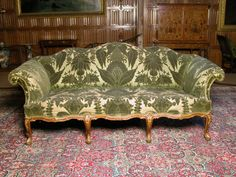 Settee - Part of a suite of early George III (c.1760) mahogany and gilt furniture on cabriole legs, with stylised acanthus decoration, upholstered in green cut silk velvet
