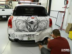 Rich using transfer tape to apply intricate cut vinyl graphics to a mini cooper. 12-Point SignWorks