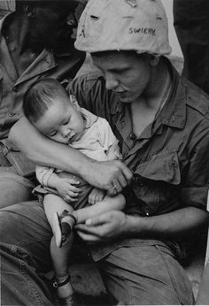 An American troop holds a young Vietnamese child who fell asleep in his arms