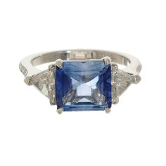 Sapphire engagement ring with diamond trillions and a pave diamond band.  Custom design collection at Greenwich Jewelers.