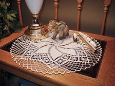 "This spiral doily with the spider-web pattern squares was an easy doily to make. I first saw the pattern at Christmas time and the center reminded me of a poinsettia and the spider-web squares looked like snowflakes. I guess it must have been the eggnog that caused the illusion! This measures 21"" wide.    The pattern named Pinwheel Doily,  in a small booklet by South Maid, 1991.  The booklet was titled  ""Timeless Doilies to Crochet"" (Article J.12 - Book 356, pub. 1991)"
