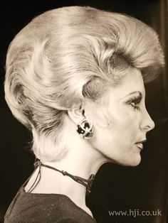Blonde short hair was brushed back for volume at the crown and the front was brushed into a quiff